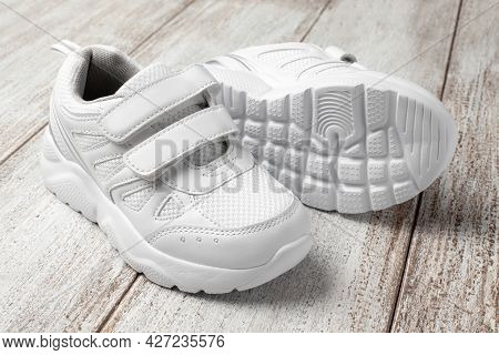 White Childrens Sneakers On A Light Background. A Pair Of Fashionable Sports Sneakers With A Velcro