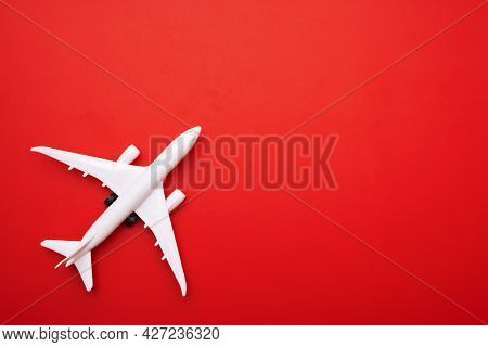 White Model Of Passenger Plane On Red Background, Travel Concept. Traveling By Plane.