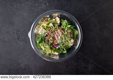Salad With Smoked Duck Breast, Vegetables, Cheese And Herbs In A Transparent Container On Dark Backg