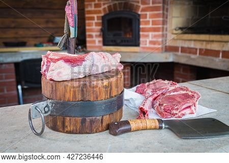 Raw Meat On A Deck, A Knife Stuck In The Meat. Fresh Meat On A Cutting Board. Close-up.