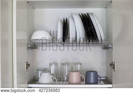 Organization For Small Spaces. Kitchen Organization. Dishes Over The Sink. Plates And Cups.