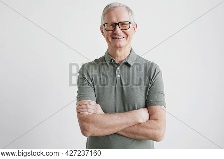 Minimal Waist Up Portrait Of Smiling Senior Man Looking At Camera While Standing With Arms Crossed A