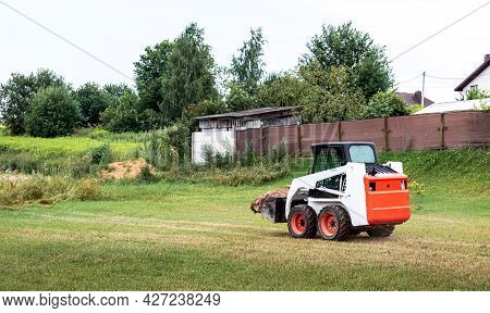 A Skid Steer Loader Clears The Site For Construction. Land Work By The Territory Improvement. Machin
