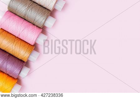 Tailor's Work Desk. Tailor Or Embroidery Background. Pattern Of Color Sewing Threads Or Reels On Pin
