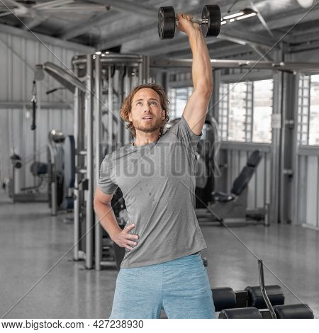 Gym workout fitness man training with dumbbells lifting overhead raise shoulders exercise shoulder press indoors at health club. Square crop.