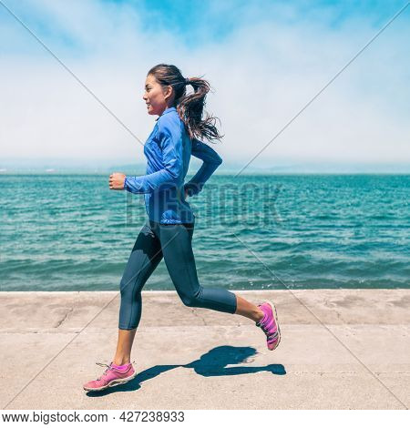 Running athlete Asian woman jogging by the beach wearing blue windbreaker jacket leggings and shoes. Training outdoor in spring by the sea. Square crop profile portrait.