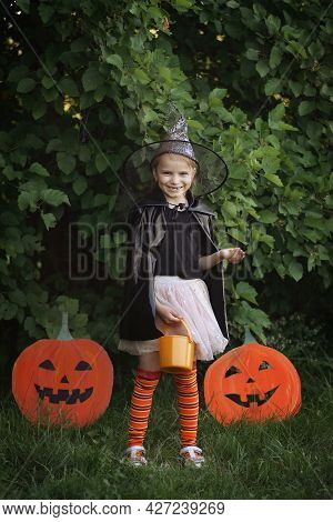 Happy Halloween Day. Portret Little Girl Dressed In Witch Costume Holds Bucket Of Candy And Fun Smil