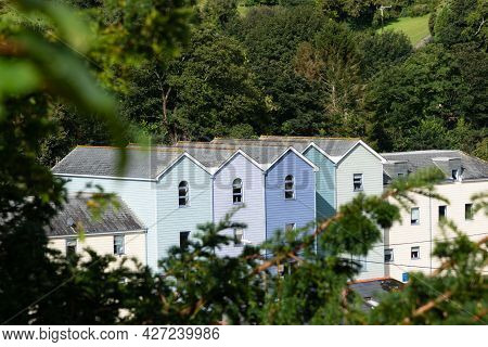 Blue House Rooftops Surrounded By Forest. Insurance, Investment, Moving House, Sale, Rent, Mortgage