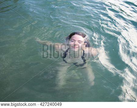 Smiling Young Woman In Black Bikini Emerging From Water