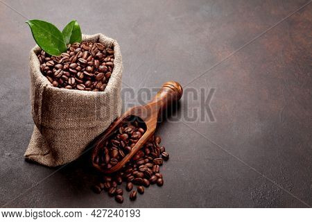 Roasted coffee beans in burlap bag and wooden spoon. With copy space