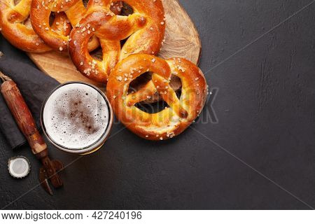 Lager beer mug and fresh baked homemade pretzel with sea salt. Classic beer snack. Top view flat lay with copy space