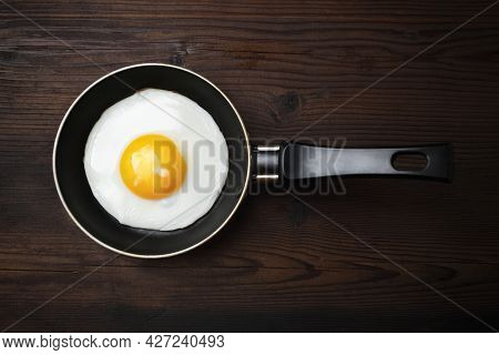 Fried Egg In Frying Pan On Wooden Background. Flat Lay.