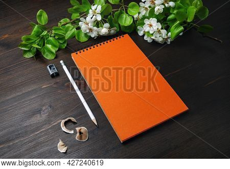 Photo Of Blank Stationery Template. Orange Sketchbook, Pencil, Sharpener And Spring Flowers On Wood