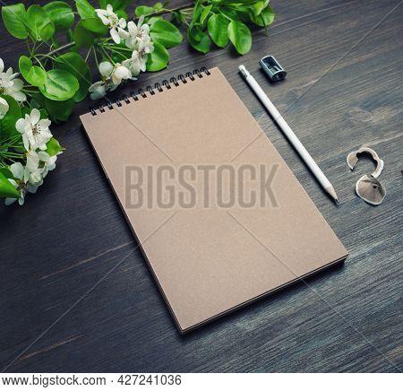 Branding Stationery Mockup. Kraft Notebook, Pencil, Sharpener And Spring Flowers On Wooden Backgroun