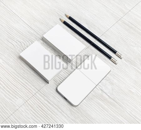 Smartphone, Blank Business Cards And Pencils On Light Wood Table Background. Branding Stationery Tem