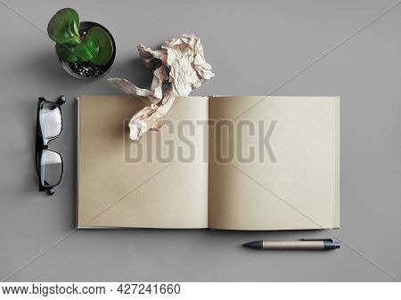 Blank Kraft Book, Stationery And Plant On Gray Paper Background. Responsive Design Mockup. Top View.