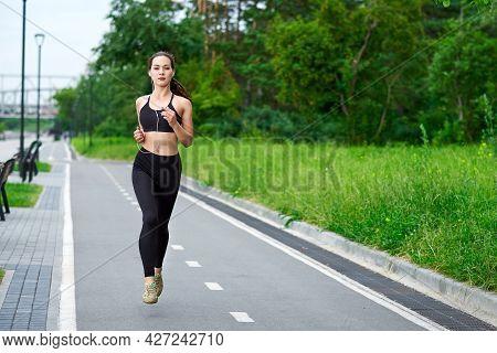 Running Asian Woman On Running Track. Morning Jogging. The Athlete Training