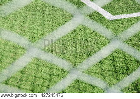 Synthetic Soccer Field Seen Through A Net. The Net And The Shadows It Casts Form Patterns Of Lines T