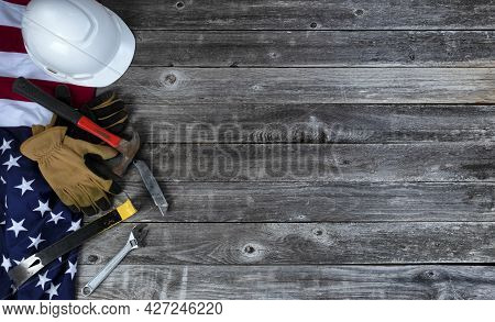 American Flag With An Assortment Of Work Tools Plus Work Gloves On Weather Old Wood For Us Labor Day