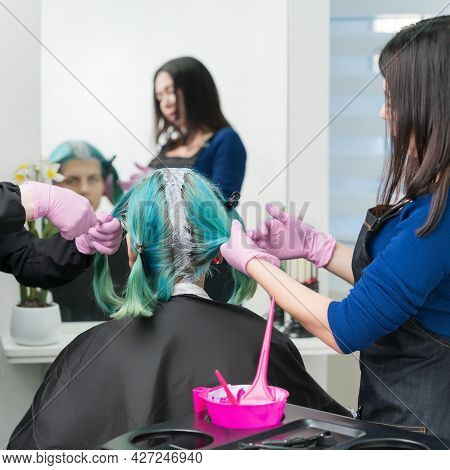 Two Master Hairdressers Apply Paint To Woman Hair During Bleaching Hair Roots. Process Of Hair Dye I