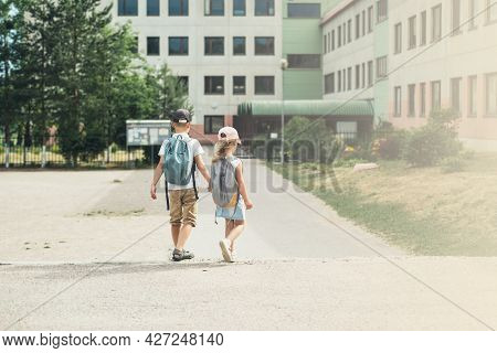 Boy And Girl, Elementary School Students,  Walking To School With Bags Behind Their Backs.  Students