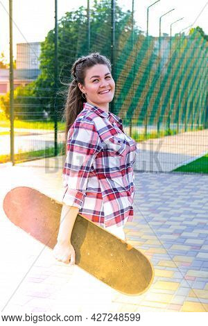 Cute Millennial Woman Smile Happy Walking Down The Street With Her Skateboard. Sun Backlight And Fre