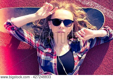 Millennial Hippie Woman With Sunglasses And Headphones Lying Down On A Skateboard On Street. Skater