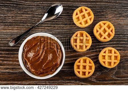 Teaspoon, White Bowl With Boiled Condensed Milk, Few Soft Biscuit Waffles Round Shape On Dark Wooden