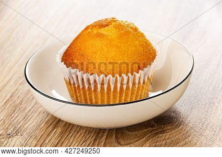Muffin In Paper Wrapper In White Glass Bowl On Wooden Table