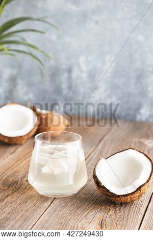 A Glass Of Fresh, Organic Coconut Water, Milk On A Wooden Table Under Palm Leaves. Chopped Juicy Coc