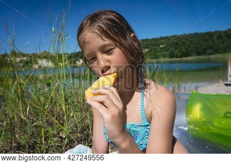 A Little Cute Girl Is Eating Her Breakfast On The Shore Of A Blue Quarry Lake.