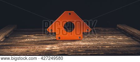 Magnetic Corner For Welding On A Wooden Background. A Studio Photo With Hard Lighting.