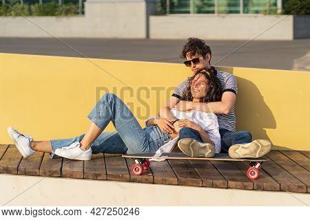 Couple In Love Enjoy Sunset Sitting Embracing On Longboard. Trendy Urban Man And Woman Wearing Styli