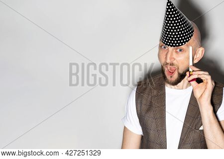 Funny Birthday. Expressive Man. Holiday Party. Funny Guy Casual Look Wearing Festive Hat Holding Whi