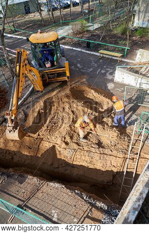 Izhevsk, Russia - May 08 2021: Modern Yellow Excavator Buries Narrow Trench During Changing Water Pi