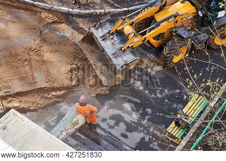 Izhevsk, Russia - May 08 2021: Workers In Uniform Bury Deep Trench With Excavator At Changing Pipeli