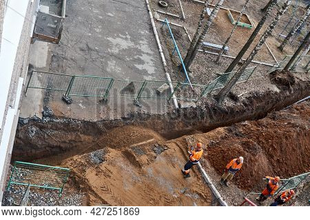 Izhevsk, Russia - May 08 2021: Team Of Workers In Uniform Stands Near Narrow Trench With New Plastic
