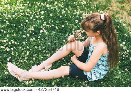 A Cute Caucasian Girl Is Sitting In A Clover Meadow And Collecting A Bouquet. Rest From The City. Th