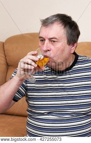 An Elderly Man Is Drinking White Wine While Sitting On The Couch. Rest And Drunkenness In Retirement