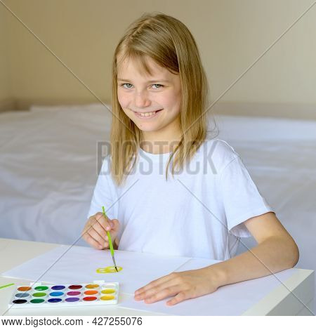The Girl Draws With Paints In A White Sunny Room. Home Art Teaching Concept. Creative Child At Work