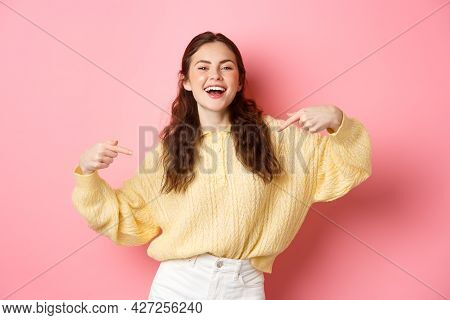 Self-assured Happy Girl Points At Herself And Laughs, Self-promoting And Smiling, Standing Against P