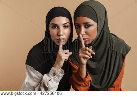 Young muslim women in hijab showing silence gesture at camera isolated over beige background