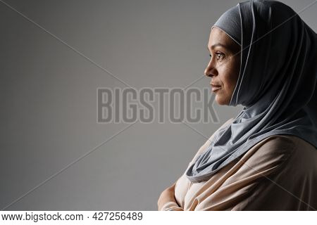 Middle eastern woman in hijab posing and looking aside isolated over grey background