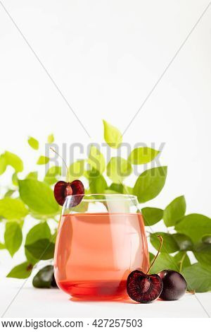 Cold Fresh Fruit Summer Layered Alcohol Cocktail With Cherry Liqueur, Ice Cubes In Glass With Sliced