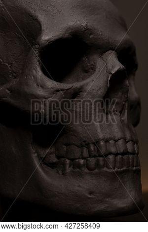 Black Concrete Skull Close Up. Bust Of The Skull. Halloween Black Decor. Minimalism In The Interior.