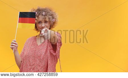 Girl Holding German Flag In Her Hand. Pointing With Her Finger At The Camera. Girl Isolated Over A Y