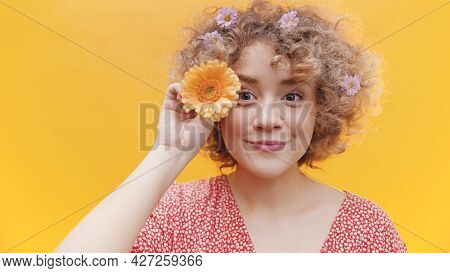 Young Attractive Girl Posing With Orange Gerbera Daisy Flower. Isolated Girl With Bright Yellow Back