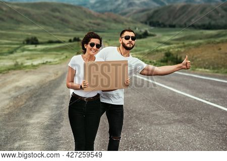 A Man And A Woman Are Hitchhiking. A Young Couple Goes Hitchhiking Around The Country. Free Hitchhik