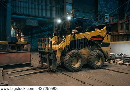 Small Loading Tractor Or Mower At Work In Metallurgical Factory Workshop.