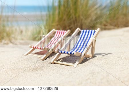Summer beach vacation, two beach deck chairs on the sand